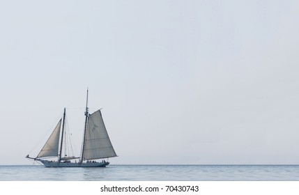 large sailing boat with guests aboard in Charleston Harbor on a clear blue day