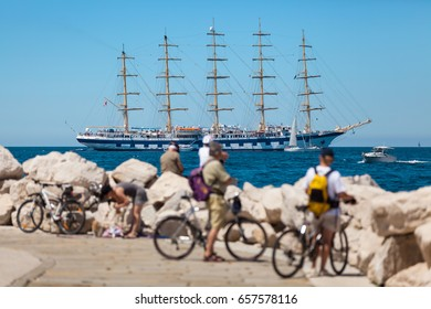 Large sailing ship with five masts anchored in the open sea near old city Piran, Slovenia. Tourists on bicycles are looking at the ship.