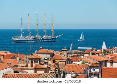 Large sailing ship with five masts anchored in the open sea near old city Piran, Slovenia.