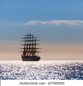 Large sailing ship with five masts leaves at sunset in the open sea.