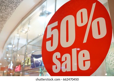 Large Sale 50% off letters on a glass wall obstruct a view inside the popular fashion store