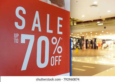 Large Sale 70% off letters on shopping mall wall pillar, bokeh shopping mall as background.