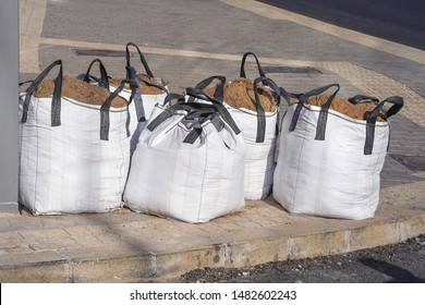 Large sandbags, construction materials for the work. Big sand bags were placed beside the road, Jumbo bags of sand are used for sandpits and under paving.