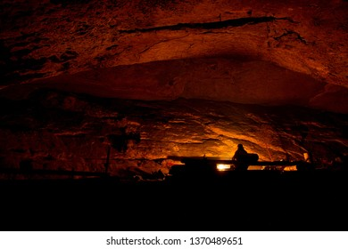 Large sandstone abri lit by campfire with a silhouette of a person in a hat sitting by the fire. Shot in the Czech republic.
