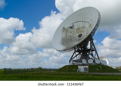 a large satellite dish with blue cloudy sky.