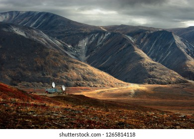 Large satellite dishes on the mountainside. Beautiful autumn tundra. Severe expressive landscape. Dark sky. A spot of light on the hillside. Egvekinot, Iskaten ridge, Chukotka, Russian Far East.