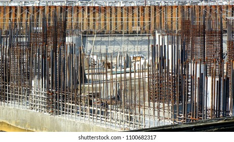 A large scale construction site with steel bars and concrete pillars