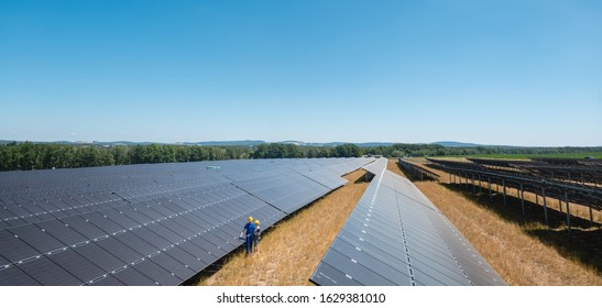 Large scale photovoltaic power plant with people standing at the panels