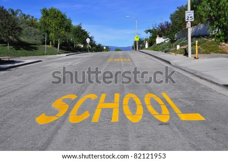"Large ""SCHOOL"" sign painted on an urban street"