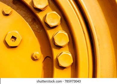 Large screw on the yellow tractor detail - powerful machinery on construction site