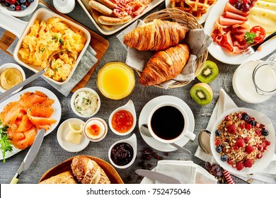Large selection of breakfast food on a table with muesli , eggs, croissant, orange juice, fruit, smoked salmon, cold meats, cheese and jam served with coffee viewed from above