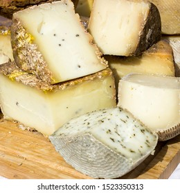 Large selection of cheese varieties on a wooden table background.