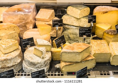 A large selection of different french and italian cheeses on  display in a French supermarket. Paris, France