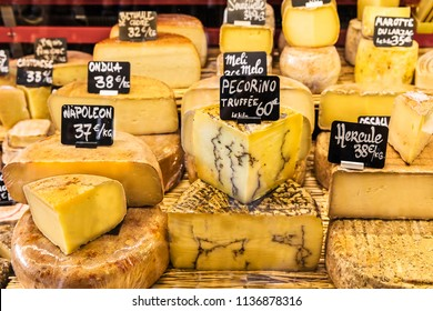 A large selection of different french and italian cheeses on the counter of a small store at the market in the Bastille district. Paris, France