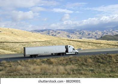 A large semi trailer rig hauls a load from California eastward into the Sierra Nevada Mountains