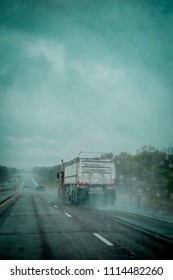 A large semi truck hauls cargo down highway 401 on a rainy spring day in Ontario, Canada. Photograph is filtered through a rain covered windshield.