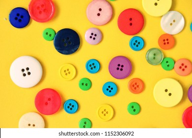 A large set of buttons in different colors and designs in front of one colored background