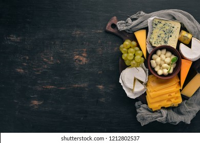 A large set of cheeses. Mozzarella, blue cheese, brie cheese, maasdam. Top view. On a black wooden background. Free space for your text.