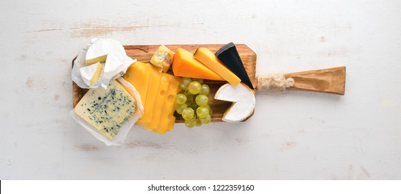 A large set of cheeses. Mozzarella, blue cheese, brie cheese, maasdam. Top view. On a white wooden background. Free space for your text.
