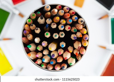 Large set of colored pencils pointing up - top view