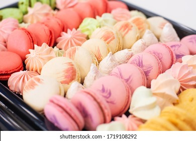 a large set of colorful macaroons and marshmallows on a holiday table