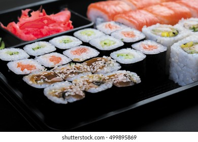 Large set of japanese rolls on a black plastic plate