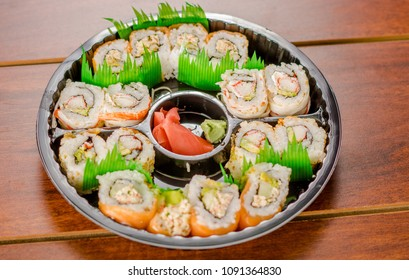 Large set of japanese sushi rolls on a black plastic plate