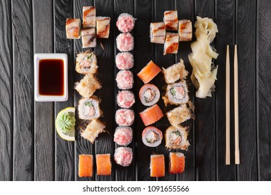 Large set of rolls with garnish and hashi on wooden plate