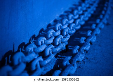 Large ship chains closeup tinted in classic blue color, symbol of strength and power