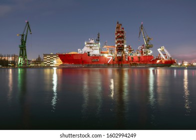 A large ship moored in the port, industrial landscape at night.