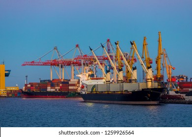 A large ship stands under cranes in the cargo port of Odessa and unloads a container with goods at sunset