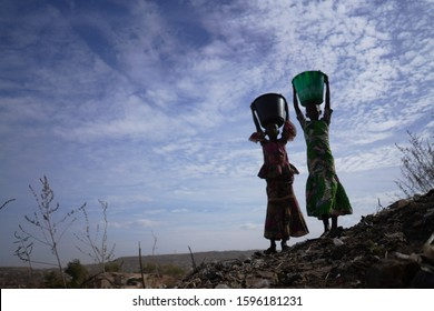 Large shot of Bamako city with two African girls Posing with Water Buckets