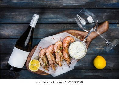 Large shrimp or langoustine with white sauce, bottle of wine, glass for the wine and half of a lemon on a wooden board. Top view