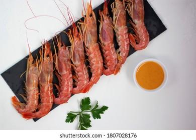 Large shrimps on a black slate board with chili mango sauce. Soft focus.