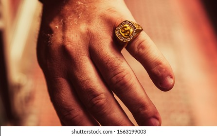 large signet ring with a $ symbol on the male hand