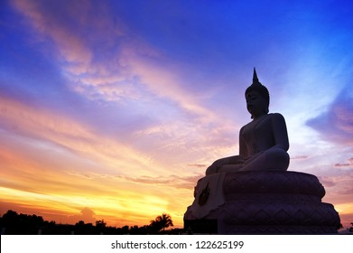 A large silhouette of Buddha, a golden Buddha sitting on a stone under the  sunrise in Thailand, Buddhism is one of the religions in Asia. Buddhists prefer to build a large Buddha image to worship.