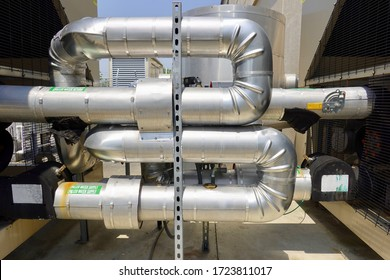 Large silver metal conduit pipes for industrial heating and cooling system.