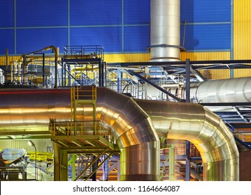 Large silver pipes of an incinerator plant at night. An incinerator plant at a canal with night blue sky.