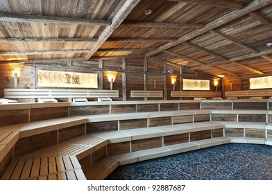 large sized  sauna made with very old wood and historical ligthning images with frames at the wall