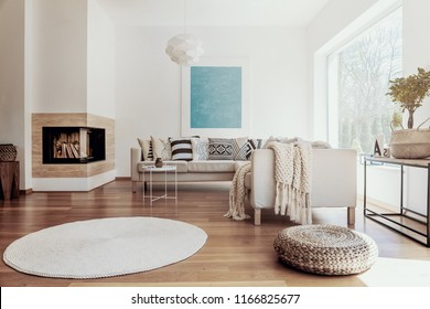 Large sky blue abstract art poster and a modern fireplace in a bright living room interior with dark hardwood floor