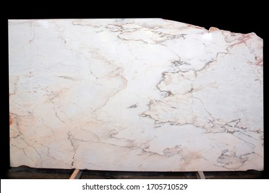 A large slab of natural pink and white striped stone is called Bianco Rosa Portugalo