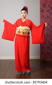 c61b759727 Large sleeves on traditional red Japanese kimono robe garment complete with  obi sash being modeled by