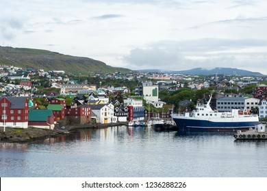 Large and small boats moored in port with colourful buildings and mountains in the background, Torshavn, Streymoy island, Faroe Islands