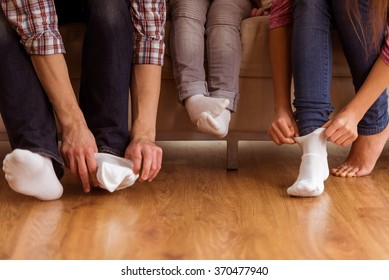 Large and small feet. Family sitting on sofa together - focus on feet. Family's feet close-up on wood floor.