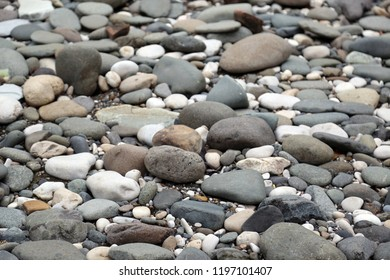 Large and small sea pebbles angle view background