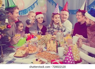 Large smiling spanish family celebrating children`s birthday during festive dinner