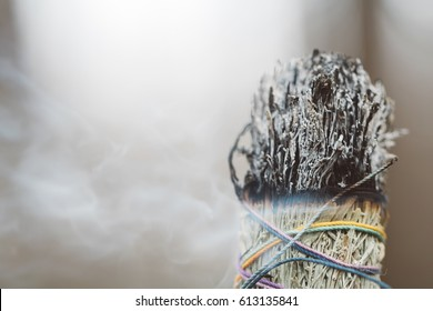 ?lose-up of a large smoking bundle of sage incense on a blurred forest background.