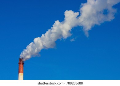 A large smoking pipe against the background of a bright, cloudless sky. Poor environmental conditions, harm to nature, harmful emissions into the atmosphere, pollution of the environment.
