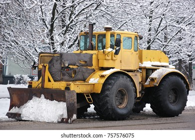 Large snow cleaning tractor with front shovel.