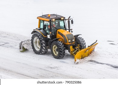 Large snow plowing tractor machine at work on the road during a snow storm in winter